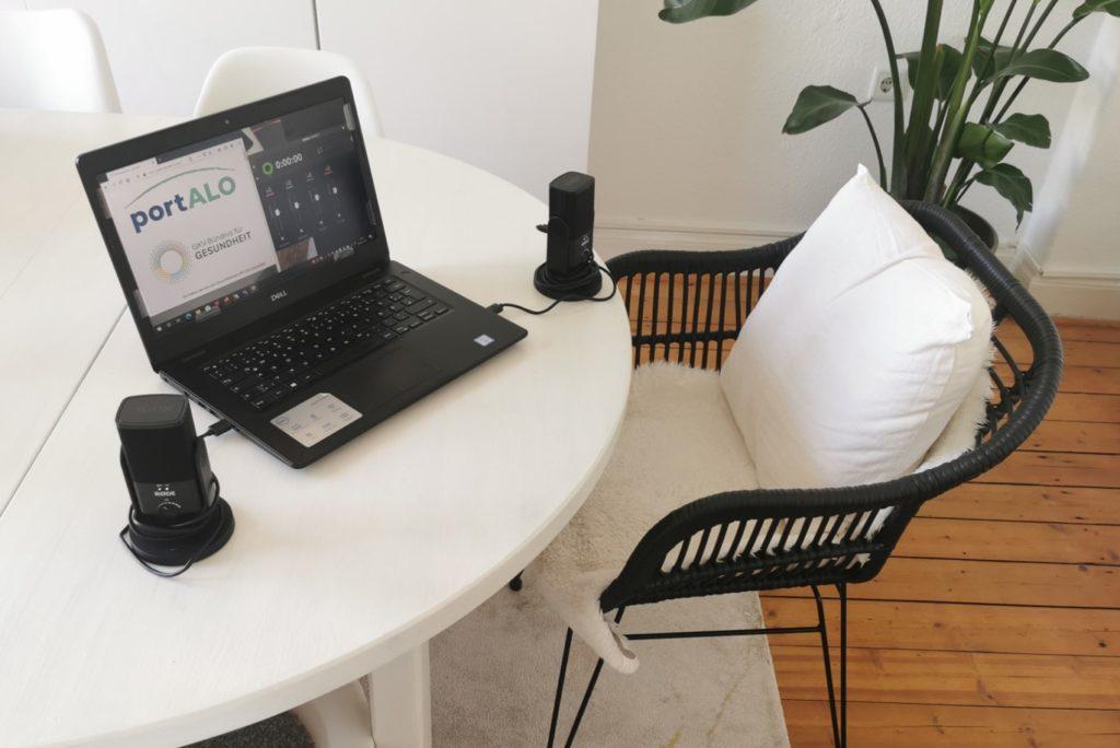 EIn Tisch und ein Stuhl. Auf dem Tisch steht ein Laptop und ein großes Mikrofon..